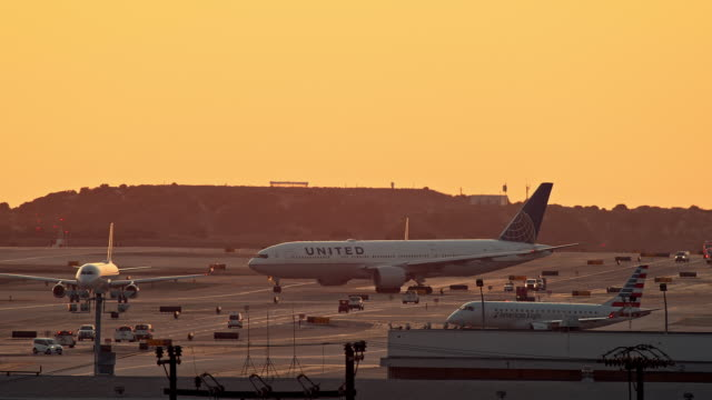 ls united airlines passenger jet taxis from gate and makes a turn to enter runway line-up of planes waiting for departure as one plane takes off and quickly ascends into sky - waiting stock videos & royalty-free footage