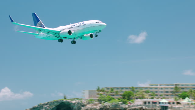 ws ts united airlines plane flying over sea and maho beach / st. maarten - beach umbrella stock videos and b-roll footage