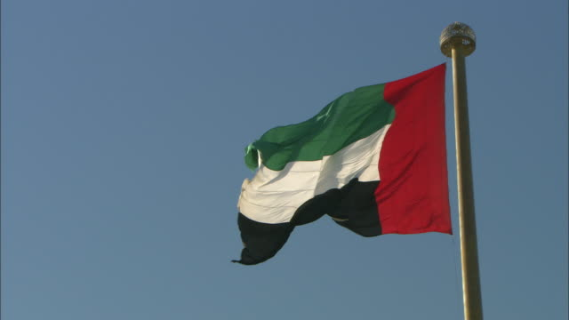 la zi cu united arab emirate flag flapping against clear sky, dubai, united arab emirates - flag stock videos & royalty-free footage