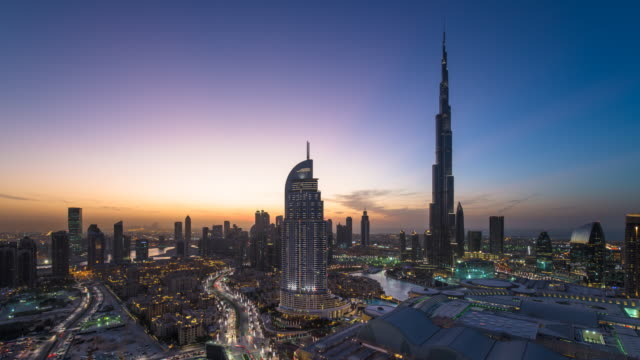 united arab emirates, dubai, elevated time lapse looking over the burj khalifa, the dubai mall, hotels and apartments - dusk to night transition - dusk to night stock videos and b-roll footage