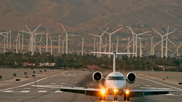 ls united express jetliner taxis on airport runway and makes right-hand turn toward airport terminal against background of large wind farm and automobile street traffic - palm springs california stock videos & royalty-free footage