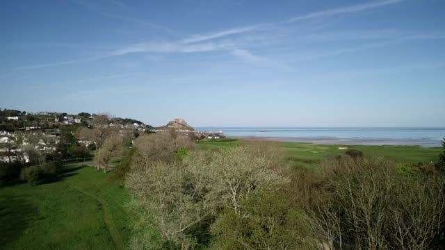 united kingdom, channel islands, jersey, gorey, royal jersey golf course, mont orgueil castle (gorey castle) - 英国海峡 チャンネル諸島点の映像素材/bロール