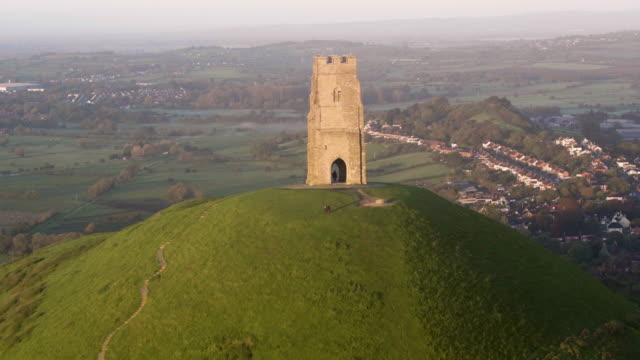 vídeos de stock, filmes e b-roll de united kingdom, england, somerset, glastonbury, st. michael's church tower on glastonbury tor - menos zoom
