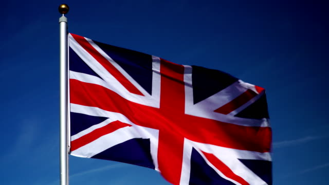 4K: United Kingdom Flag on Flagpole in front of Blue Sky outdoors (UK)