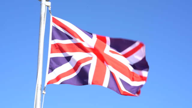 united kingdom flag with clear blue sky background - bandiera del regno unito video stock e b–roll