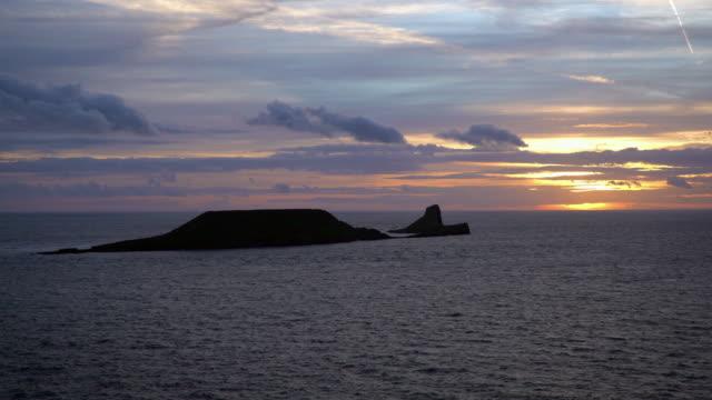vídeos y material grabado en eventos de stock de united kingdom, south wales, gower peninsular, sunset over worms head - península de gower