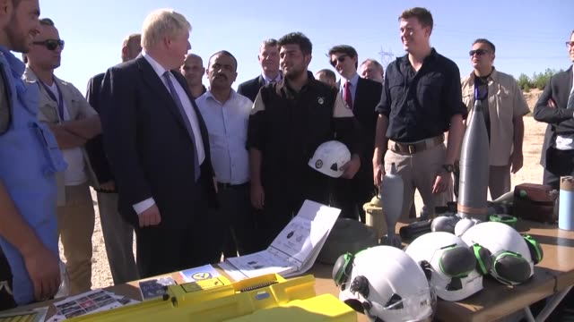 United Kingdom's Foreign Minister Boris Johnson is informed by Syrians who are being educated by British bomb disposal experts during his visit the...