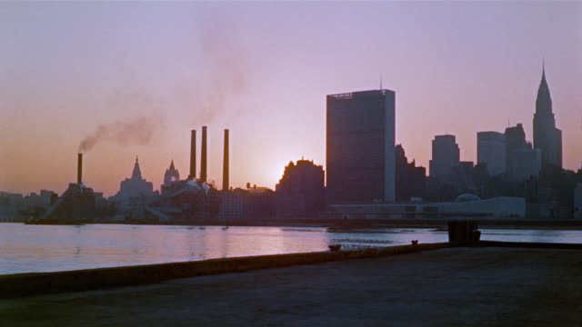 1959 MONTAGE WS United Nations building and smokestacks at sunset with East River in foreground / New York City