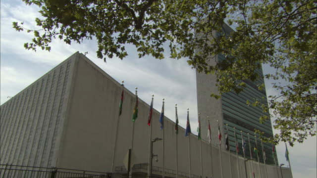 ws la united nations headquarters with flags in foreground / new york city, new york, usa - united nations building stock videos and b-roll footage