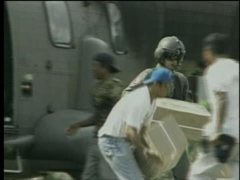 united nations helicopter crewmen and indonesian locals unload relief supplies following the indianocean tsunami in 2005 - healthcare and medicine or illness or food and drink or fitness or exercise or wellbeing video stock e b–roll