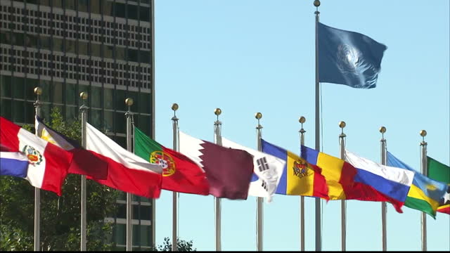 CLEAN United Nations members flags blowing in wind outside United Nations Headquarters in New York Countries include Iran Peru Philippines Poland...