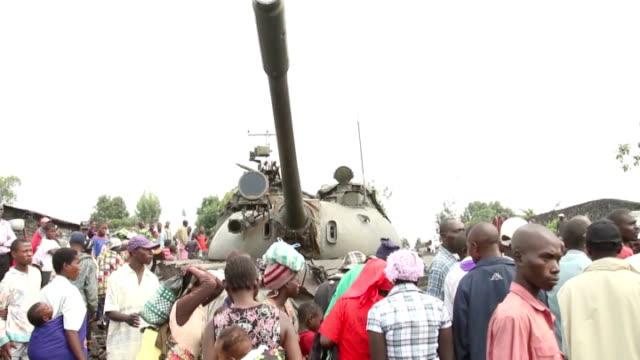 united nations report links senior rwandan minister with m23 rebels democratic people standing around abandoned tank damaged car in street - コンゴ民主共和国点の映像素材/bロール