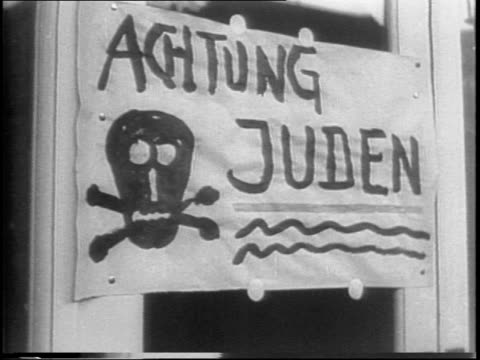 united nations / row of international flags / archival footage from 1938 / sign reads 'achtung juden' / broken window of jewish shop / nazi guards... - judaism stock-videos und b-roll-filmmaterial