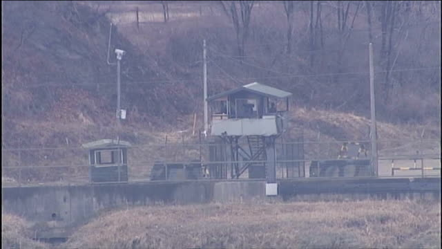 vídeos y material grabado en eventos de stock de united nations says north korea must 'calm down' korean watchtowers or checkpoints at demilitarized zone man looking through telescope - corea