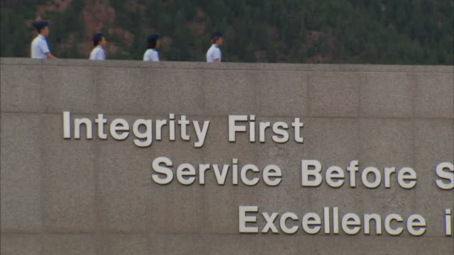 united states air force academy students walk above a sign displaying air force values: integrity first, service before self, excellence in all we do. - bildungseinrichtung stock-videos und b-roll-filmmaterial