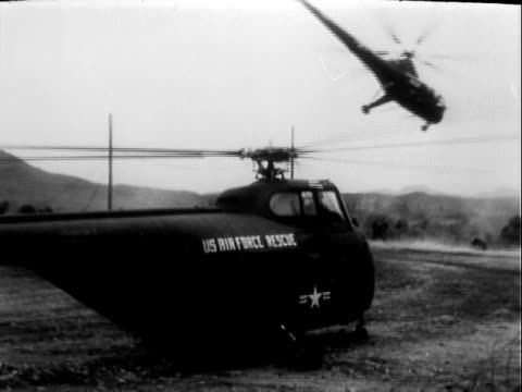 vidéos et rushes de united states air force airmen standing beside usaf rescue helicopter air base in south korea / usaf sikorsky h5 dragonfly rescue helicopter lifting... - 1953