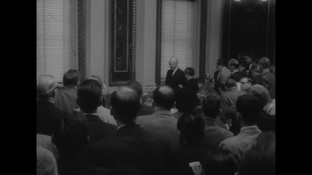United States Capitol Building / VS journalists cameramen lights behind / assembly rises as President Eisenhower enters room with aides begins press...