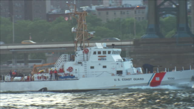 a united states coast guard cutter sails under the brooklyn bridge, and past a sightseeing boat, as it moves on the east river near the franklin d. roosevelt east river drive. - coast guard stock videos & royalty-free footage