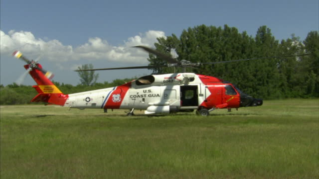 united states coast guard uscg sikorsky hh60j jayhawk w/ rotors turning sitting in grass field chopper lifting off hovering above take off spot - helicopter rotors stock videos and b-roll footage