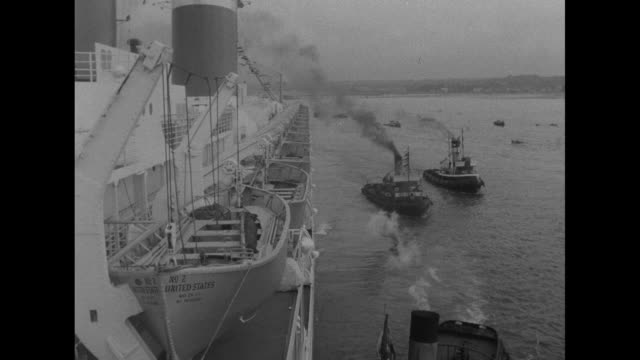 united states enters harbor at southampton, escorted by smaller boats / from ship's prow as it advances / side deck of the ss united states, with... - ship's bow stock videos & royalty-free footage