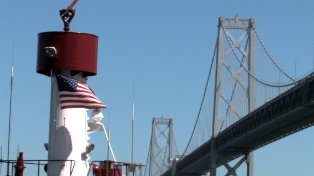 米国の旗とサンフランシスコ・ベイブリッジ - サンフランシスコ・オークランド・ベイブリッジ点の映像素材/bロール