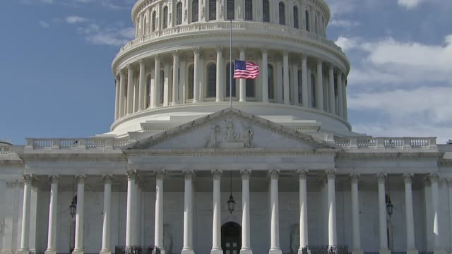 a united states flag flies halfmast below the dome of the capitol building as the late reverend billy graham lies in honor in the rotunda - kuppeldach oder kuppel stock-videos und b-roll-filmmaterial