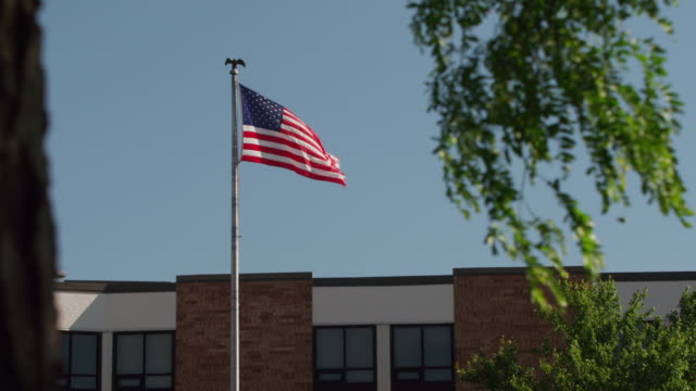 united states flag furls from a flagpole topped with an eagle in front of a public school. - etablera scenen bildbanksvideor och videomaterial från bakom kulisserna