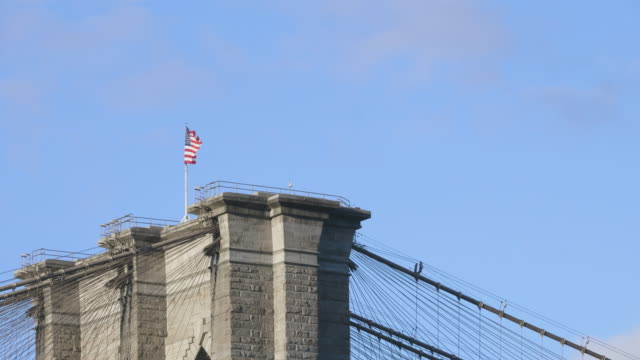 united states flag on top of brooklyn bridge - flag blowing in the wind stock videos & royalty-free footage