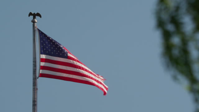 a united states flag with frayed edges blows in the wind from a flagpole topped by an eagle. - ausgefranst stock-videos und b-roll-filmmaterial