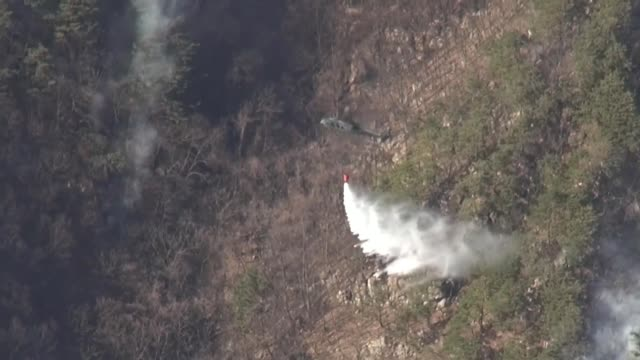 stockvideo's en b-roll-footage met united states forces korea are supporting firefighting efforts with uh60m black hawk helicopters by dropping water on designated areas to contain and... - overheersing