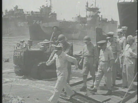 United States General Douglas MacArthur walking off landing craft on Labuan beach greeting shaking hands w/ Australian officer on beach LA MS...