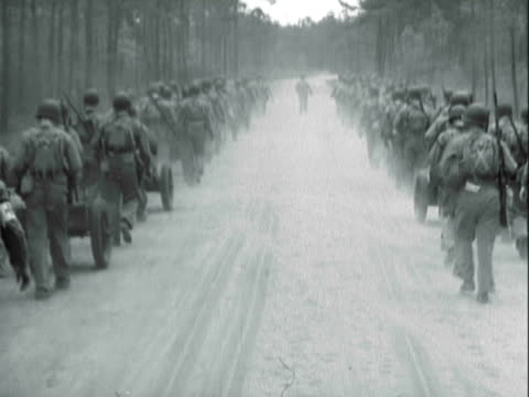 MONTAGE United States Marine Corps trainees marching along dusty rural road / United States
