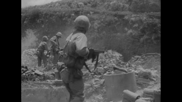 vídeos de stock e filmes b-roll de united states marines at cave entrance on hillside / they remove round cover to reveal two japanese toddlers sitting in box / vs marines carry the... - world war ii