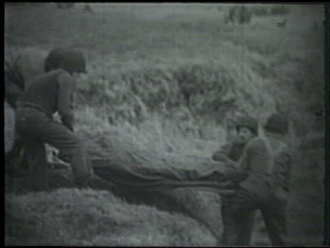 stockvideo's en b-roll-footage met united states marines carrying wounded soldier in stretcher down field wounded soldier lying down w/ other soldiers sitting wwii world war ii pacific... - alaska verenigde staten
