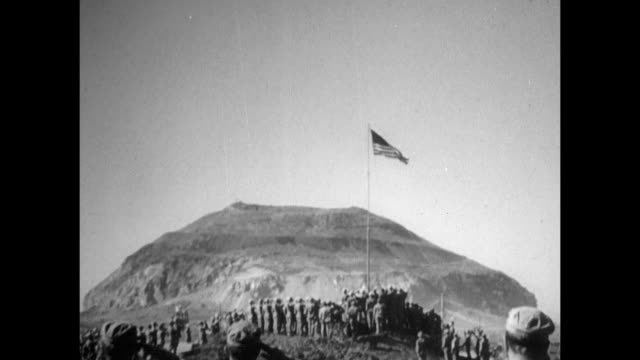 xws united states marines during flag ceremony at northern iwo jima american flag raising on pole mountain bg / vs us marines planting cross in... - battle of iwo jima stock videos & royalty-free footage