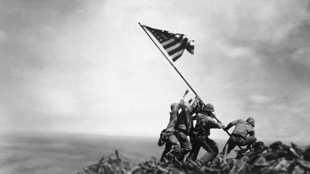 united states marines raise the american flag on mount suribachi after the battle of iwo jima. - battle of iwo jima stock videos & royalty-free footage