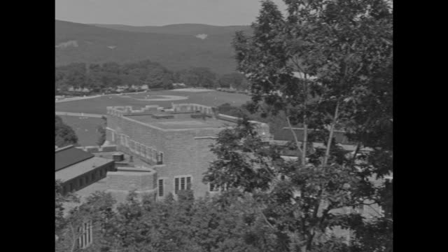 United States Military Academy with Pocono Mountains beyond / structure on lake / men and one woman on raft with divers / couple lying prone on stone...