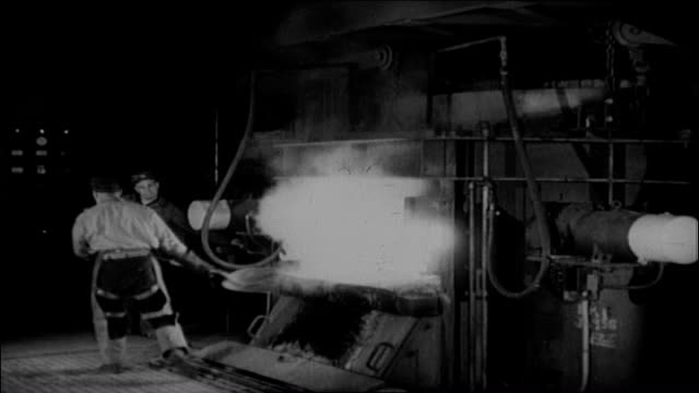 "United States Naval Gun factory Molten steel sparking workman in silhouette Young adult Caucasian male worker shovels coal into furnace 3"" 50 caliber..."