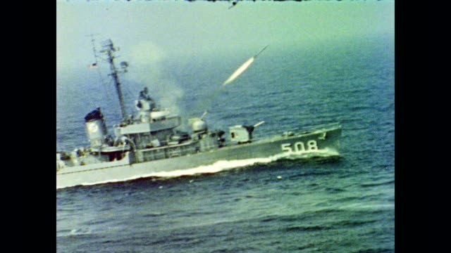 United States Navy destroyer ships on ocean fire missiles during torpedo training