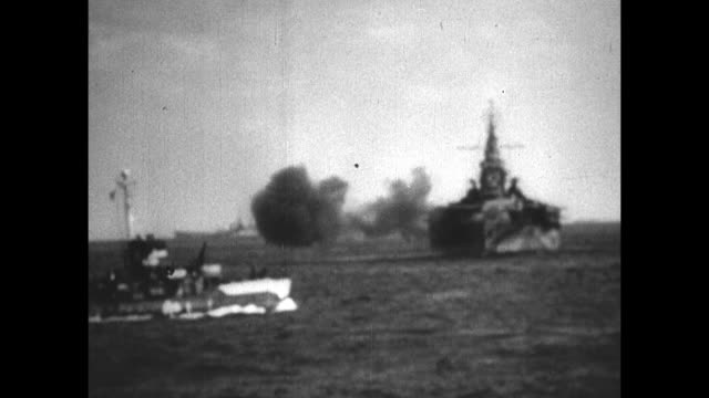 VS United States Navy warships battleships firing on island of Iwo Jima explosion smoke on island / VS Navy officers on deck watching bombardment of...