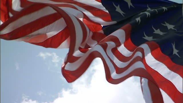 HD TU CU SLO MO United States of America country flag flying on flag pole waving in ripples against blue sky clouds BG