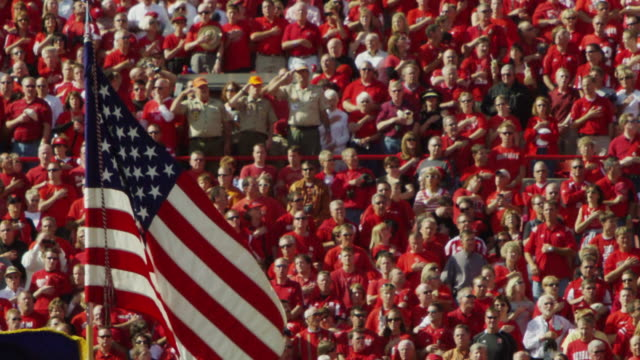 "A United States of America, flag waves proudly as football spectators in the background put their hand over their hearts at the end of the ""Pledge of Allegiance."""