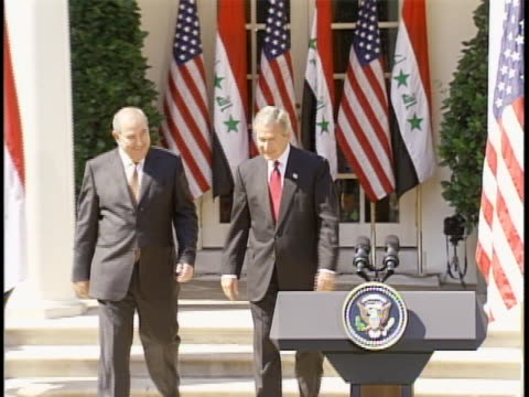 united states president george w. bush and iraq prime minister ayad allawi walk outside of the white house toward the podiums for a white house rose... - 2000年風格 個影片檔及 b 捲影像