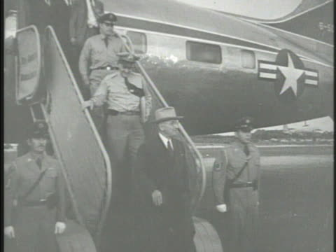 United States President Harry S Truman walking down steps from airplane greeting General Douglas MacArthur posing for press photographs VS Bunker...