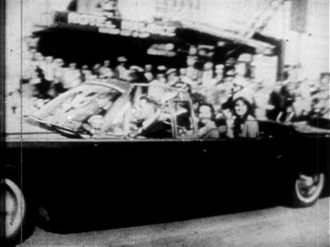 united states presidential motorcade traveling through downtown dallas dealey plaza president jfk others riding in uncovered limousine passing crowds... - attentat auf john f. kennedy stock-videos und b-roll-filmmaterial