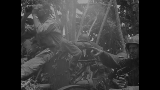 vs united states troops advance across field at base of ridge gunfire and shelling / two soldiers look over bay / ls over water shells from ship's... - united states marine corps stock-videos und b-roll-filmmaterial
