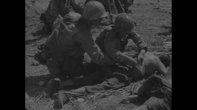 vídeos de stock, filmes e b-roll de vs united states troops process japanese prisoners of war they sit clad in loincloths in clusters on ground in open field/ pow drinks from canteen /... - crachá