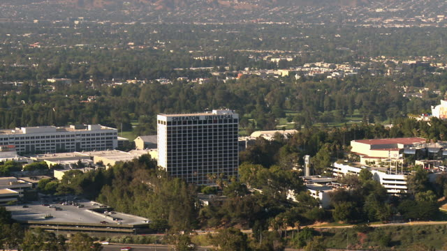 ws pan universal city with sheraton and hilton hotels on property of universal studios and universal citywalk amusement park area and burbank with warner brothers and disney studios in background / universal city, california, usa - warner bros stock videos & royalty-free footage