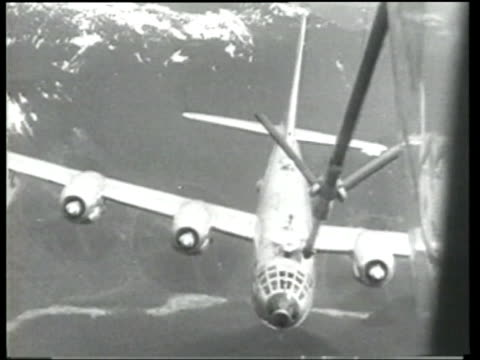 A boom operator concentrates as a B29 bomber is refueled at high altitude above snow covered mountains