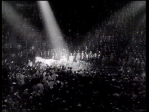 A dapple gray mare pulls US President Dwight and Mamie Eisenhower in a Pennsylvania buggy into an auditorium where a giant cake celebrates the...